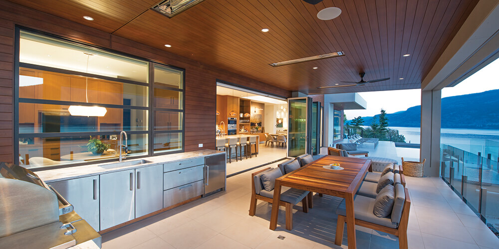 Folding doors open up the living space to an outdoor kitchen and dining area with additional seating for guests. AD905