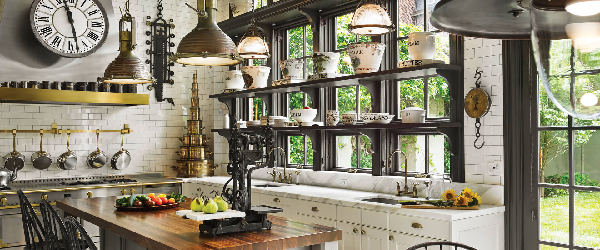 Many stationary picture and transom windows stacked over Ultra Series crank-out awning windows behind a kitchen counter.