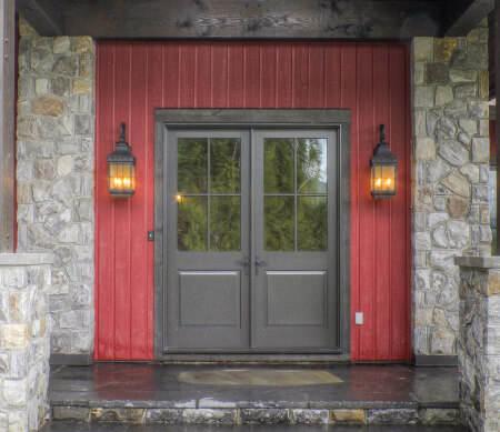 Ultra Series inswing French entrance doors with Truffle exterior finish, extruded aluminum raised panels and glass lites with PDL bars.