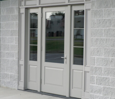 Ultra Series outswing commercial door with sidelites and extruded aluminum raised panels with Sand exterior finish.