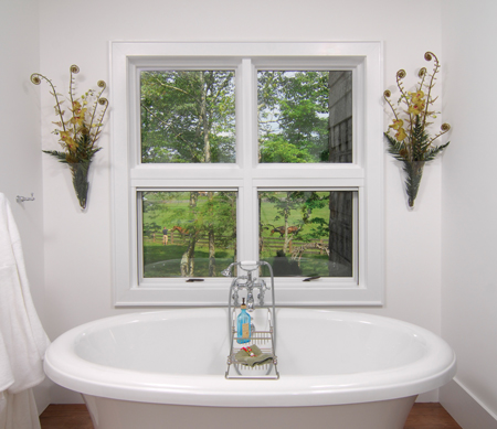 An Ultra Series awning window unit with two stationary windows on top and two push-out windows on bottom, near a bath tub.