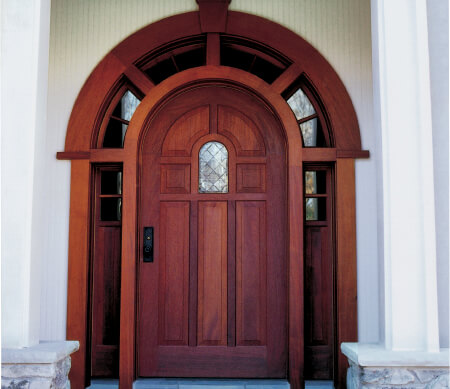 Heritage Series Mahogany inswing entrance door with raised panels, custom sidelites and transoms.